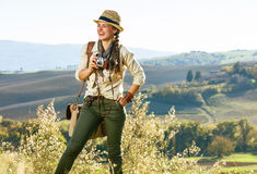 Smiling woman hiker on Tuscany hike with vintage photo camera Stock Photos