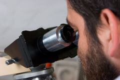 Discovery. Scientist looking into microscope ocular Stock Images