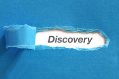 Discovery. Appearing behind blue color paper stock photo