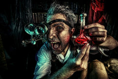 Discovery. Portrait of a crazy medieval scientist working in his laboratory. Alchemist. Halloween royalty free stock image