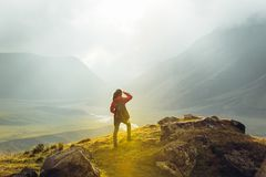 Discovery Travel Destination Concept. Hiker Young Woman With Backpack Rises To The Mountain Top Against Backdrop Of Sunset, Rear V. Young girl on foot hiker with stock photos