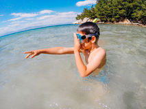 Discovery. A young boy swimming with goggles pointing as if he made a discovery royalty free stock photo