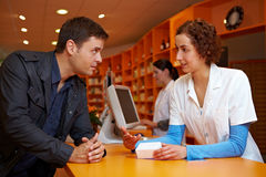 Discrete talk in pharmacy Stock Image