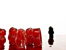 Discrimination. Group of red jelly-babies with isolated black jelly-babies, depicting discrimination Stock Image