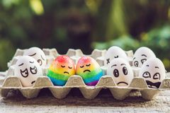 Discrimination gay concept. Two rainbow eggs in the form of a homosexual couple. And condemning people around.  royalty free stock images