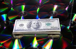 Discs. One Hundred Dollar Bills On Some Colorful Compact Discs Stock Photos