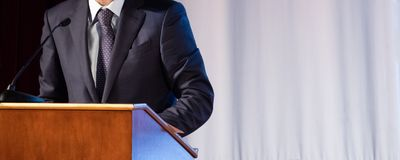Discurso de um homem abstrato em um terno na fase no suporte para desempenhos Tribuna ou cathedra para o oficial do orador, presi foto de stock