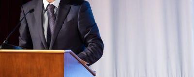 Discurso de un hombre abstracto en un traje en etapa en el soporte para los funcionamientos Tribuna o cátedra para el funcionario foto de archivo