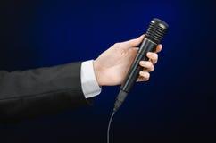 Discurso e assunto do negócio: um homem em um terno preto que guarda um microfone preto em uma obscuridade - fundo azul no estúdi Imagem de Stock
