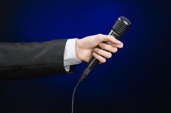 Discurso e assunto do negócio: um homem em um terno preto que guarda um microfone preto em uma obscuridade - fundo azul no estúdi Fotos de Stock