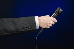 Discurso e assunto do negócio: um homem em um terno preto que guarda um microfone preto em uma obscuridade - fundo azul no estúdi Imagens de Stock