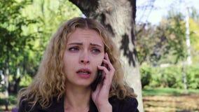 Discurso gritador de la muchacha en el teléfono que se sienta en un banco en el parque metrajes