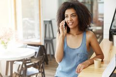 Discurso sonriente de la muchacha africana hermosa alegre feliz en el teléfono que se sienta en café Imágenes de archivo libres de regalías
