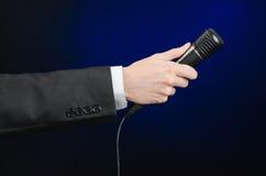 Discurso y tema del negocio: un hombre en un traje negro que sostiene un micrófono negro en un fondo azul marino en estudio aisla Imagen de archivo