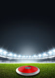 Discus In Generic Floodlit Stadium. A discus in a generic stadium resting on an unmarked green grass pitch at night under illuminated floodlights vector illustration