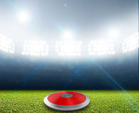 Discus In Generic Floodlit Stadium. A discus in a generic stadium resting on an unmarked green grass pitch at night under illuminated floodlights stock illustration