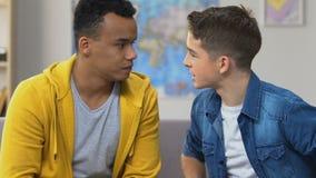 Discusión de dos adolescentes, sentándose en el sofá, problemas de la relación de la escuela secundaria almacen de video