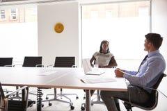Discussão de And Businesswoman Having do homem de negócios em torno da tabela da sala de reuniões na sala de reunião fotografia de stock royalty free