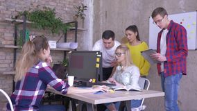A discussão do negócio, colegas de trabalho novos fala com o associado do escritório que trabalha no computador filme