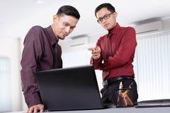Discussão dos homens de negócios sobre o portátil Fotografia de Stock Royalty Free