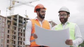 Discussão masculina de sorriso do coordenador de construção com o arquiteto no canteiro de obras ou no terreno de construção da c vídeos de arquivo