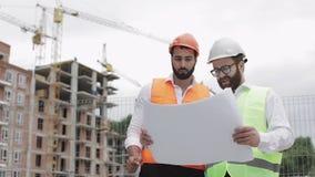 Discussão masculina do coordenador de construção com o arquiteto no canteiro de obras ou no terreno de construção da construção h vídeos de arquivo