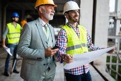 Discuss?o dos coordenadores de constru??o com os arquitetos na constru??o ou no terreno de constru??o foto de stock