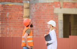 Discuss progress project. Construction industry concept. Woman engineer and bearded brutal builder discuss construction stock photography