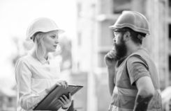 Discuss progress project. Construction project inspecting. Safety inspector concept. Woman inspector and bearded brutal royalty free stock photo