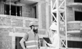 Discuss progress project. Safety inspector concept. Woman inspector and bearded brutal builder discuss construction. Progress. Construction project inspecting royalty free stock photo