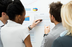 Discussing annual report. Group Of Business People Analyzing Graph and Annual Report Stock Image