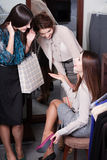 Discussing bargains while trying on new shoes. Women discuss bargains while trying on new fuchsia shoes Royalty Free Stock Photo