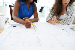Discussing blueprint. Female engineer and project manager discussing blueprint Royalty Free Stock Photos