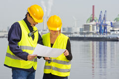 Discussing blueprints. Two engineers, wearing safety gear, including goggles, hard hat, ear plugs and reflective safety vests, discussing blue prints in an Royalty Free Stock Photos