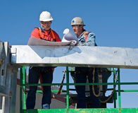 Discussing the Blueprints. Construction superintendent discussing the blueprints with a worker Stock Image