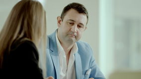 Discussing business project. Businessman and his team discussing a business project sitting at a table in office stock footage