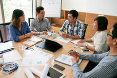 Discussing business strategy. Asian business people discussing strategy of development Stock Image