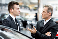 Discussing car features. Stock Photo