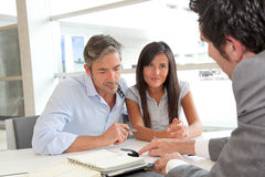 Discussing contract conditions. Father and girl signing loan contract Stock Photography