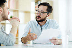 Discussing contract. Two managers discussing financial documents at meeting Royalty Free Stock Photo