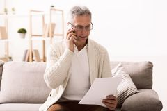 Discussing document. Mature man holding paper and talking on phone. Sitting on couch at home stock photo