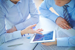 Discussing document in touchpad. Two employees discussing business document in touchpad at meeting Royalty Free Stock Images