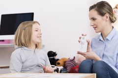 Discussing drawing during play therapy. Child counselor discussing drawing with smiling girl during play therapy stock photography