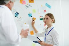 Discussing evidence. Young specialist consulting with her experienced colleague while pointing at one of evidence of crime on board royalty free stock photo