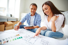 Discussing flat plan. Portrait of young couple sitting in their new flat and discussing its plan Royalty Free Stock Photos