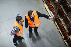 Discussing goods. Two dispatchers looking at shelf with goods for wholesale Stock Photo