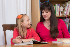 Discussing homework. A young girl shares an idea with her mother while doing homework Stock Images