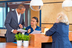 Discussing issues with a secretary. Coworkers discussing small matters with a secretary at a reception desk of a large corporate company Royalty Free Stock Photos