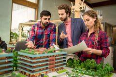 Discussing layout. Group of three young professional architects working with layout of new city district Royalty Free Stock Photography