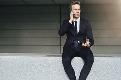 Discussing man wearing suit sits on brick Royalty Free Stock Image